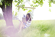 Woman relaxing with tablet in a hanging chair under a tree - MAEF011947