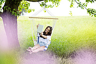 Happy woman taking selfie with tablet in a hanging chair under a tree - MAEF011950
