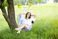 Happy woman relaxing in a hanging chair on a meadow - MAEF011953