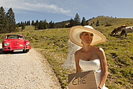 Bride waiting wayside of a pasture while groom sitting in his red vintage car - FC001065