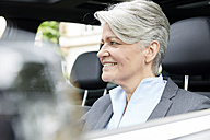 Portrait of smiling businesswoman sitting in a car - FMKF003034