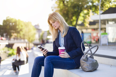 Blond businesswoman with coffee to go looking at smartphone - NAF000015