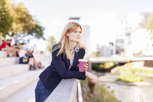 Businesswoman with coffee to go leaning on railing looking at distance - NAF000027
