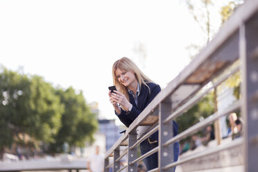 Businesswoman leaning on railing looking at cell phone - NAF000030