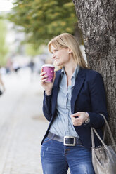 Smiling blond businesswoman with coffee to go leaning against tree trunk - NAF000036