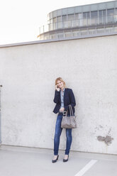 Smiling blond businesswoman on the phone standing in front of wall - NAF000039