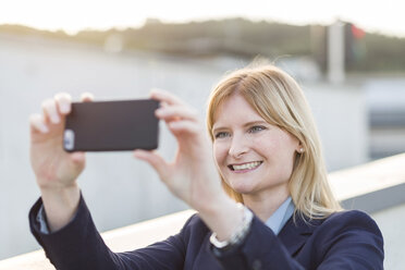 Portrait of smiling blond businesswoman taking selfie with smartphone - NAF000042