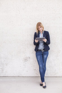 Smiling businesswoman leaning against wall looking at tablet - NAF000045