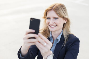 Portrait of smiling blond businesswoman taking selfie with smartphone - NAF000054