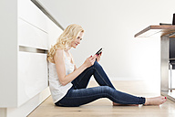 Woman sitting on floor in kitchen reading e-book - SHKF000639