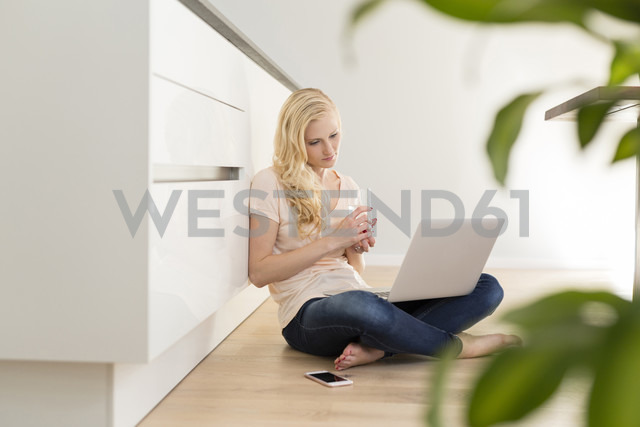 Woman sitting on floor in kitchen using laptop - SHKF000642