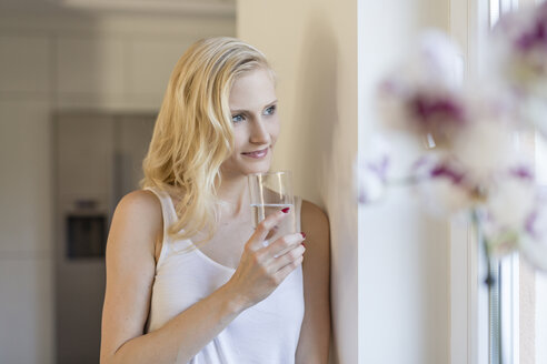 Blond woman holding glass of water at the window - SHKF000651