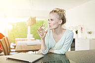 Woman in kitchen drinking glass of water - SHKF000660