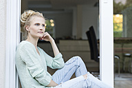 Blond woman sitting at terrace door - SHKF000663