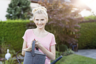 Portrait of blond woman holding watering can in garden - SHKF000669