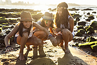 Three happy girls on the beach at sunset - MGOF002278