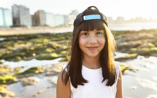 Portrait of a smiling girl on the beach at sunset - MGOF002287