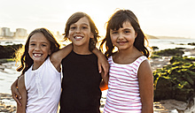 Portrait of three happy kids on the beach at sunset - MGOF002296