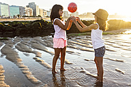 Two girls playing with a ball on the beach at sunset - MGOF002305