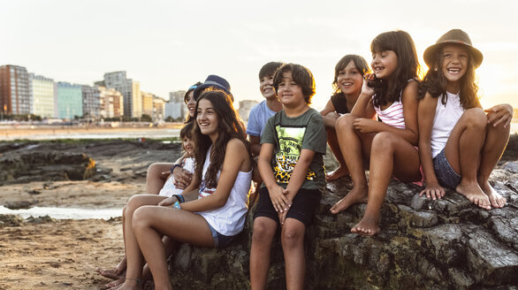 Group of kids sitting on rock on the beach at sunset - MGOF002311