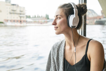 Relaxed woman listening music with headphones - TAMF000568