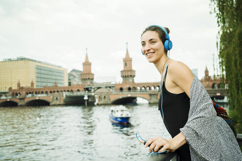 Germany, Berlin, relaxed woman listening music with headphones looking at distance - TAMF000574