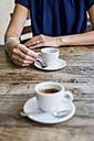 Woman drinking espresso in a sidewalk cafe, partial view - MAUF000843
