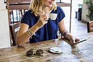 Woman drinking espresso in a sidewalk cafe looking at cell phone, partial view - MAUF000846