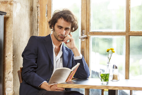 Young man in a coffee shop reading a book - TAMF000579