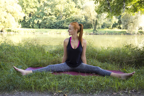 Young woman stretching on gym mat on a meadow - YFF000560
