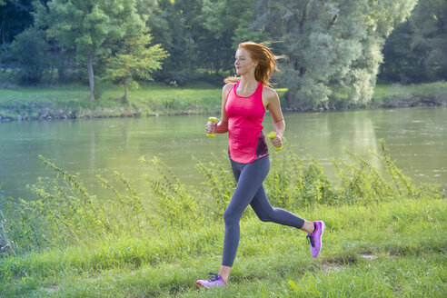 Young woman jogging with dumbbells at the riverside - YFF000566