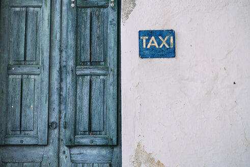 Greek, Cyclades, blue wooden door and taxi sign on the facade - GEMF000985
