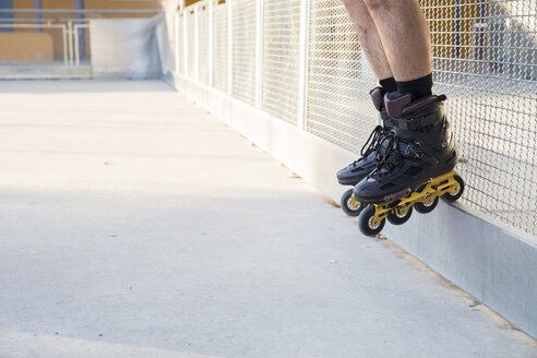 Legs of a man with rollerblades on a railing - ABZF001017