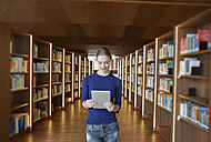 Young woman using tablet in library - FMKF003042