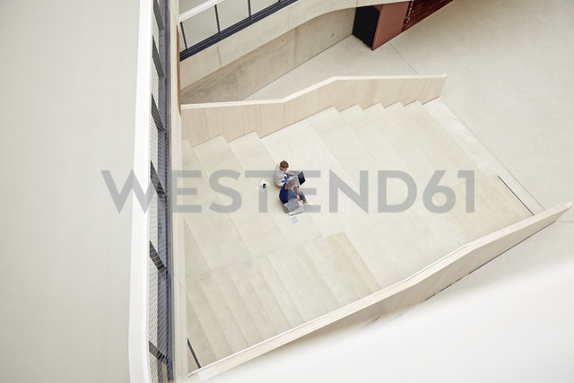 Young man and woman sitting on staircase in a building using laptop - FMKF003054