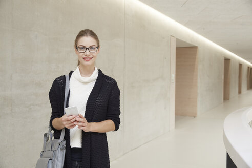 Smiling young woman on corridor of building - FMKF003063