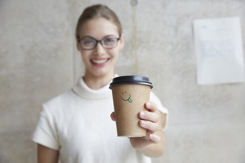 Young woman holding coffee to go cup with smiley face on it - FMKF003075