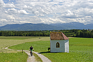 Germany, Bavaria, Faistenberg near Beuerberg, Cyclist at Otthof chapel - LBF001460