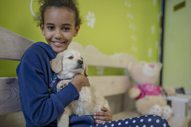 Girl holding labrador puppy at the veterinarian - ZEF009822