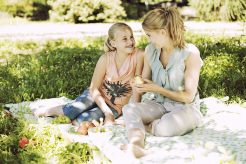 Smiling girl and young woman sitting face to face on blanket in a park - GDF001110