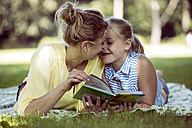 Happy girl and young woman with book lying on blanket in a park - GDF001116