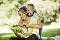 Girl and young woman with book on blanket in a park - GDF001119