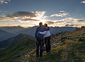 Happy couple kissing at sunset in the mountains - MKFF000332