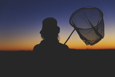 Female hiker carrying dip net at dawn - MIDF000786