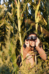 Woman hiding in cornfield and watching something with binoculars - MIDF000789
