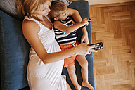 Pregnant mother and her little son lying on the couch watching TV - ZEDF000285