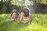 Two girls lying side by side on a meadow - LVF005226