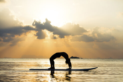 Thailand, man doing yoga on paddleboard at sunset, bridge position - SBOF000177