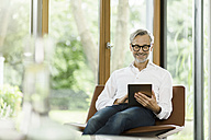 Smiling man sitting on chair in his living room using tablet - SBOF000183