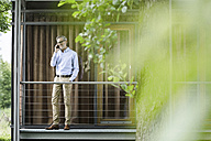 Man on the phone standing on balcony of his house - SBOF000189